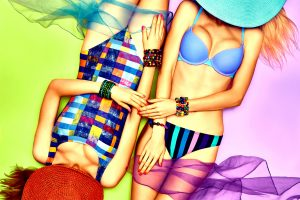 two woman in neon bathing suites laing next to each other