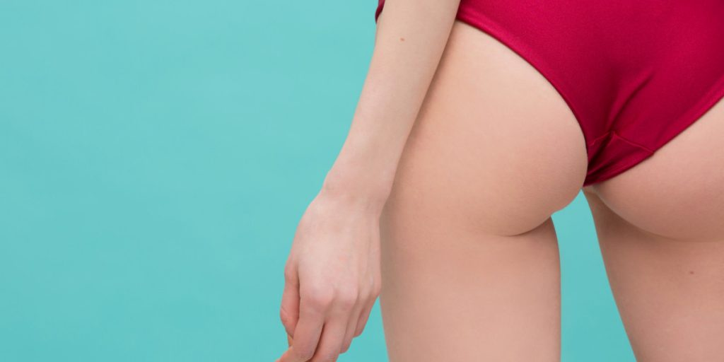 woman in red bathing suit bottom and a teal background