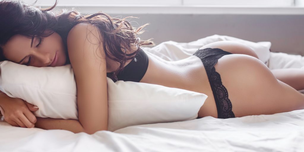 woman in black lingerie laying on a pillow on a bed