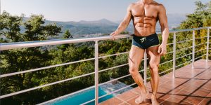 ripped man with small swim trunks on a deck
