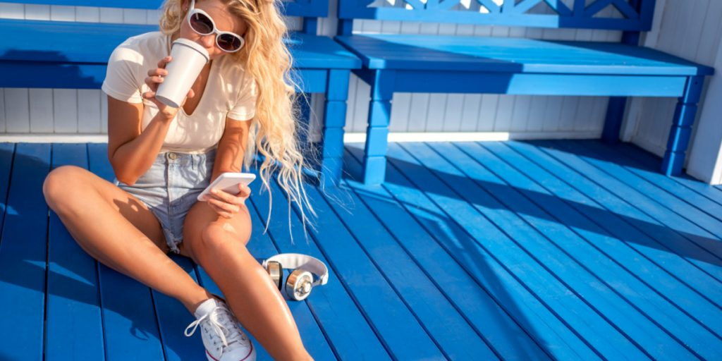 blonde woman on her phone sitting on a blue deck