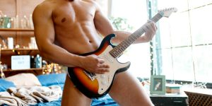 naked man playing the electric guitar