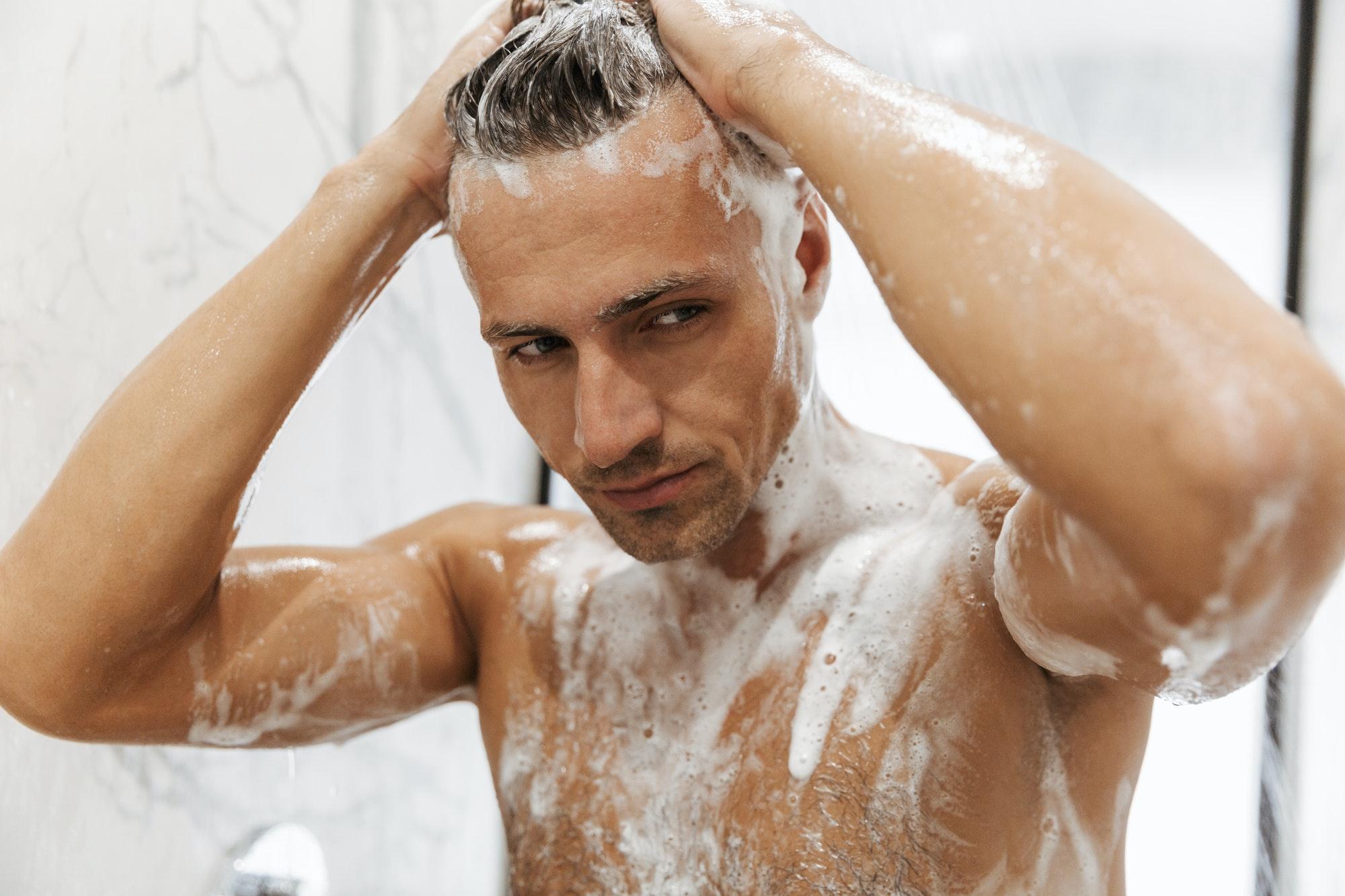 Close up of a confident man having a shower