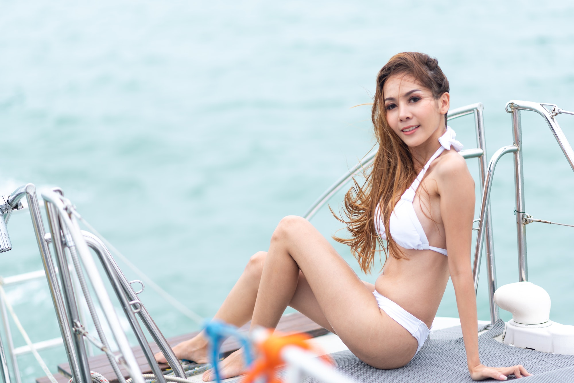 Sexy Asian woman in a bikini on a yacht, summer concept