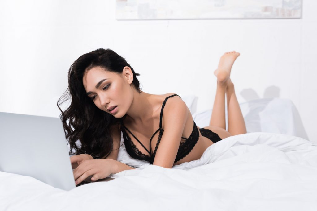 young beautiful woman in sexy lingerie using laptop in bed