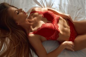 Pretty girl wearing red lingerie lying on bed